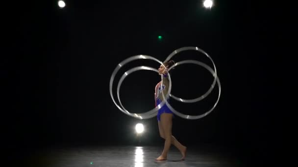Gymnast turns hoops on her arms and serves up a new one in a vertical string. Slow motion. Side view. Black background