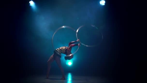Acrobat führt mit Reifen. Blauer Rauch Hintergrund. Slow-motion