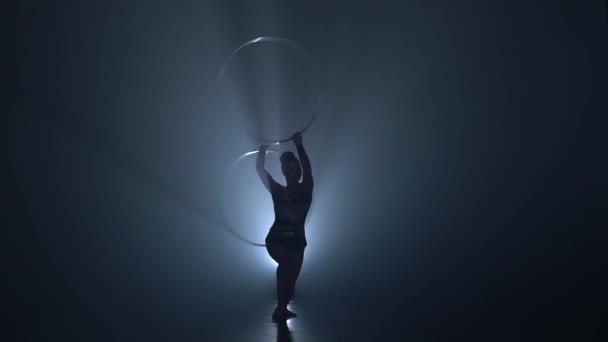 Turnerin in der Luft dreht Reifen mit den Händen. Slow-Motion. Hintergrund zu rauchen. Silhouette