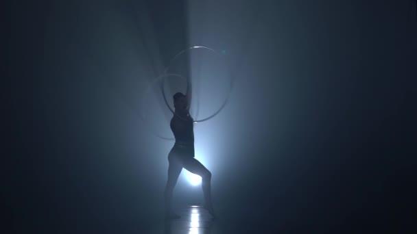 Turnerin dreht sich die Reifen auf ihre Arme und Bein erhebt. Slow-Motion. Hintergrund zu rauchen. Silhouette