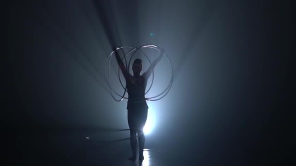 Turnerin in der Luft dreht Metall Reifen mit den Händen. Slow-Motion. Hintergrund zu rauchen. Silhouette