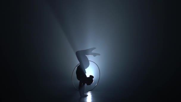 Turnerische Kunststücke, während sie auf den Händen steht, drehen den Reifen ihres Beines in die Luft. Rauchentwicklung. Zeitlupe. Silhouette