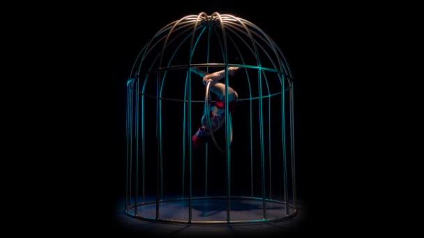 Gymnastka na obruč ve vzduchu provádí různé akrobatické kousky. Černé pozadí. Zpomalený pohyb