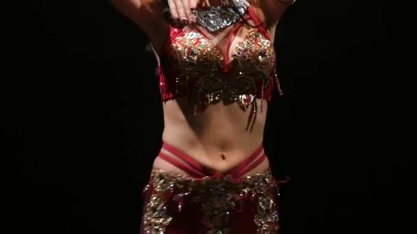 Frau führt Bauchtanz in orientalischer Tracht auf. schwarzer Hintergrund. Zeitlupe. Nahaufnahme