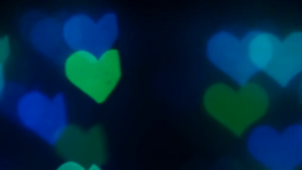 Absztrakt fények a szív alakú, fekete képernyőn. Bokeh háttér. Lassított mozgás