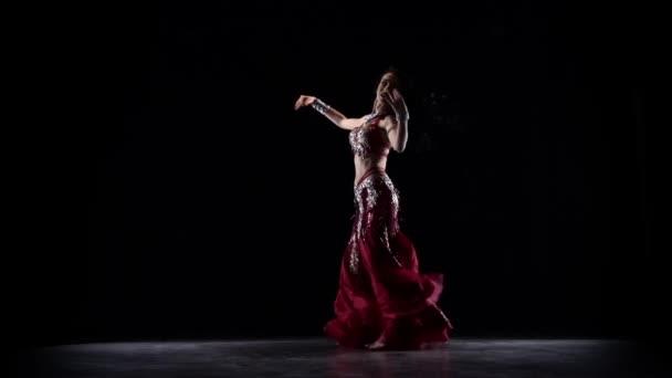 Oriental belly dancer woman dancing . Black background. Slow motion
