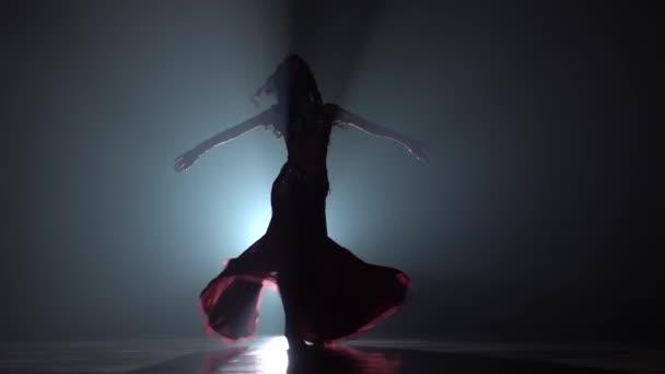 Tradiční orientální břichová tanečnice tančí na pozadí kouře. Tady sihouette. Zpomaleně