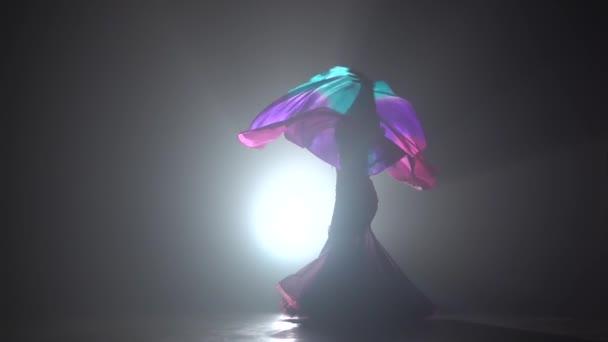 Exotická břišní tanečnice pokračuje v tanci používá fanoušky. Tady sihouette. Černý kouřový pozadí. Zpomaleně