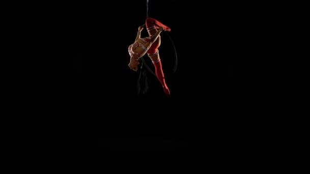 Dívčí akrobatka v červeném leotardu převrácená noha visí na vzdušném rámu na černém pozadí