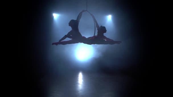 Dvě ženy se houpou na obručí a dělají gymnastické prvky na vzdušné obručí. Černý kouřový pozadí. Silueta