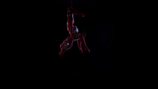 Dvě ženy se houpou na obručí a dělají tělocvičnu na vzdušné obručí. Černé pozadí. Zpomaleně