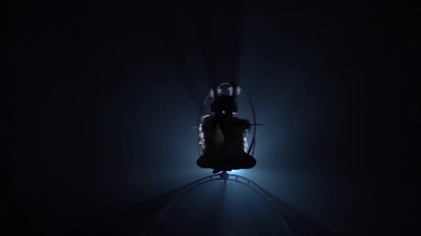 Mädchen Luftakrobaten drehen sich in der Luft auf einem Metallrahmen. schwarzer Rauchhintergrund. Silhouette. Zeitlupe