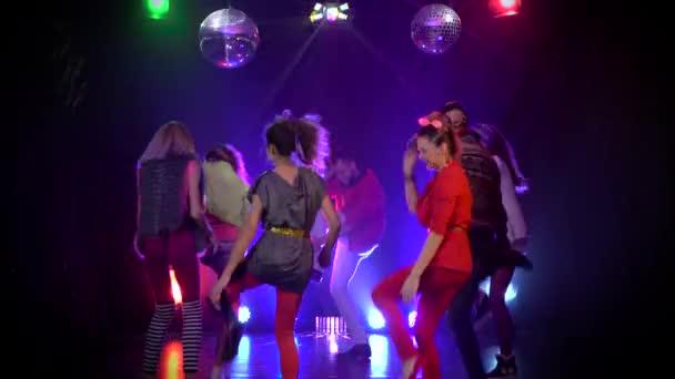 Persone gioiose e danzanti in un nightclub incandescente luci stroboscopiche. Sfondo fumo