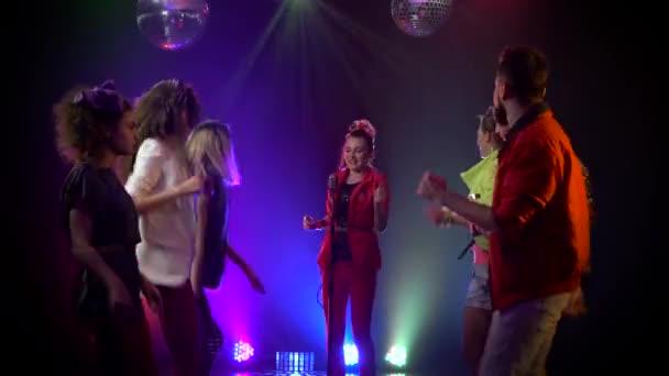 Lány énekel egy retro mikrofon körül táncoló emberek énekelni. Füstös háttér