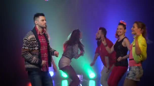 People joyful and dancing at a nightclub glowing strobe lights. Smoke background