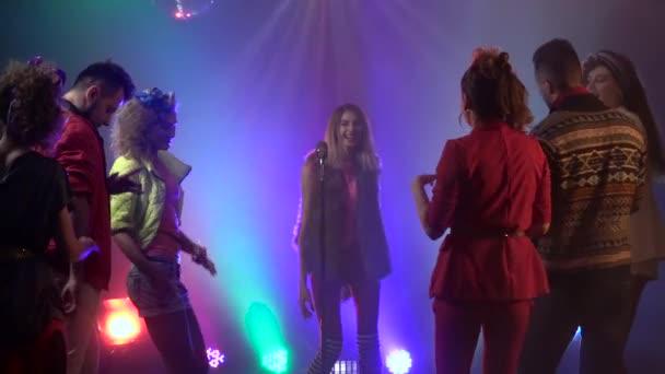 Zpěvák do retro mikrofonu kolem lidí tančících na její zpěv. Kouřové pozadí. Zpomaleně