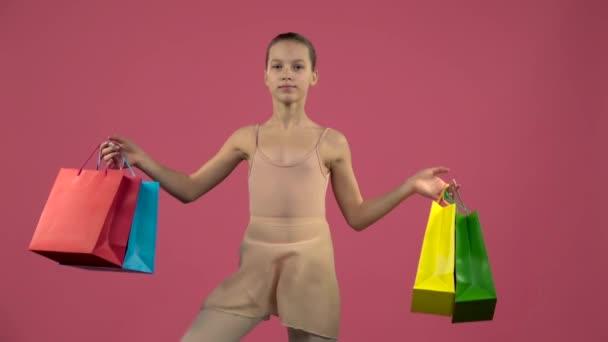 Dětské tanečnice v kostýmu se odrazí na místě s nákupní tašky. Růžový pozadí. Zpomalený pohyb