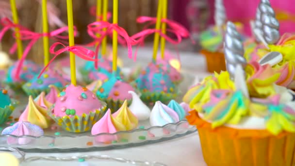 Decorated childrens birthday party. Unicorn themed treats, close-up against colorful background.