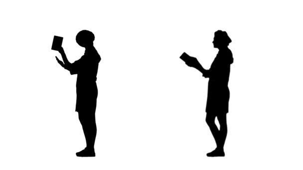 Dvě černé siluety kuchaře, jak čte knihu s recepty.