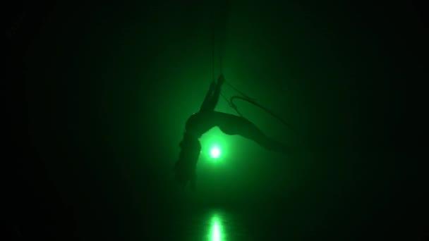 Luftakrobat im Ring. Ein junges Mädchen führt die akrobatischen Elemente im Luftring auf grünem Hintergrund 011