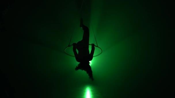Luftakrobat im Ring. Ein junges Mädchen führt die akrobatischen Elemente im Luftring auf grünem Hintergrund 012