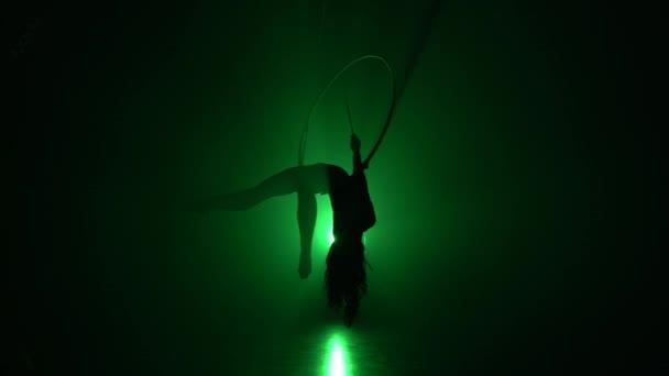 Luftakrobat im Ring. Ein junges Mädchen führt die akrobatischen Elemente im Luftring auf grünem Hintergrund 013