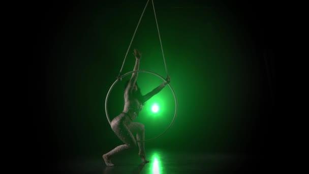 Luftakrobat im Ring. Ein junges Mädchen führt die akrobatischen Elemente im Luftring auf grünem Hintergrund 014