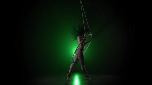 Luftakrobat im Ring. Ein junges Mädchen führt die akrobatischen Elemente im Luftring auf grünem Hintergrund 015