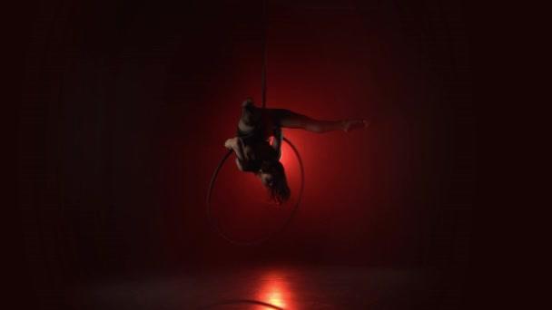 Luftakrobat im Ring. Ein junges Mädchen führt die akrobatischen Elemente im Luftring auf rotem Hintergrund 021