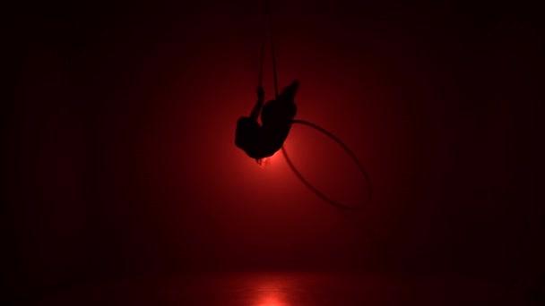 Luftakrobat im Ring. Ein junges Mädchen führt die akrobatischen Elemente im Luftring auf rotem Hintergrund 023
