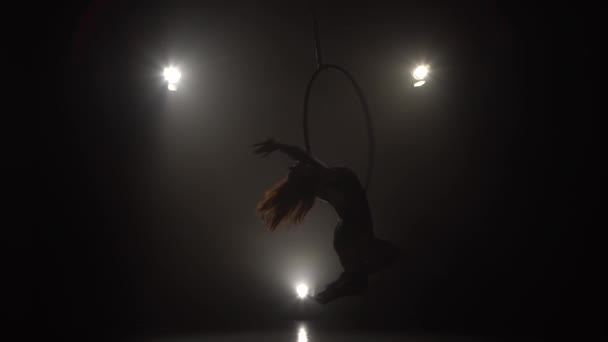 Silhouette young caucasian brunette sportive dancer female balancer in beige leotard back lying hang on aerial hoop on three rays of light background 031
