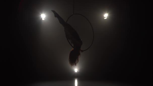Silhouette junge kaukasische Brünette sportliche Tänzerin weibliche Balancer in Beige Trikot zurück liegen dliegt hängen auf Luftreifen auf drei Strahlen des Lichthintergrunds 032