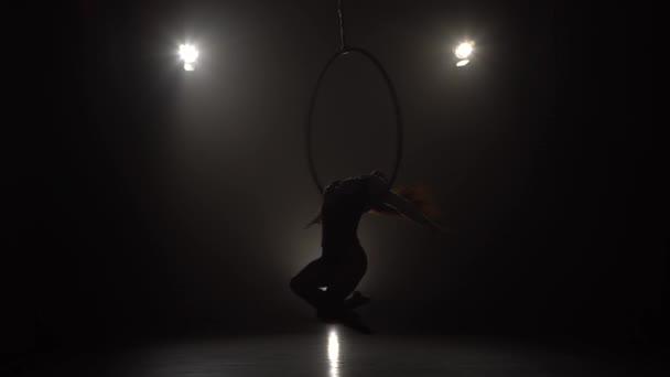 Silhouette junge kaukasische Brünette sportliche Tänzerin weibliche Balanceakrobatik im beigefarbenen Trikot Rücken liegend auf Antennenreifen auf drei Lichtstrahlen Hintergrund 033