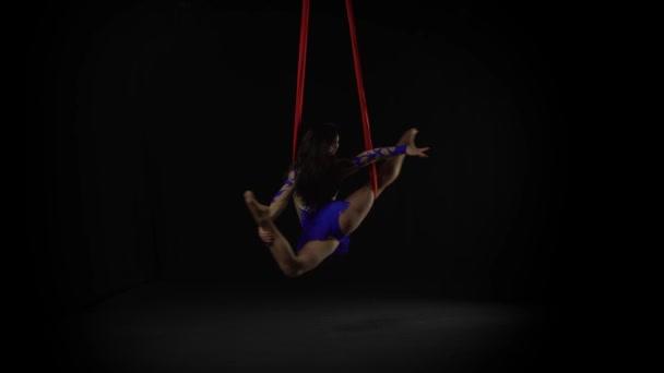 Fekete háttéren piros selyemből végzett női légi tornász. Izgalmas akrobatikus show 059