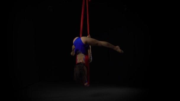 Fekete háttéren piros selyemből végzett női légi tornász. Izgalmas akrobatikus show 061
