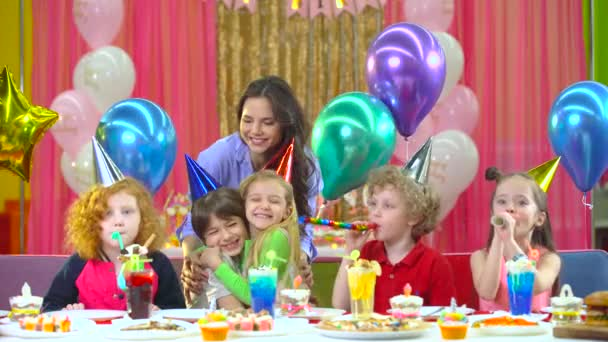 Děti v barevných kloboucích, oslavujících narozeniny matkou a snoubenkou.
