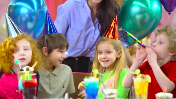 Children in colorful hats celebrating birthday with mother and fiends.