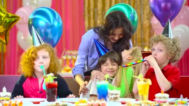 Gyermekek ünnepli születésnapját az anya és a vőlegény a kávézóban.