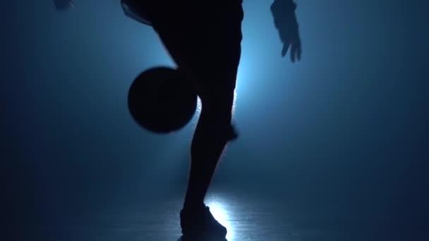 Football freestyle. Close-up of guy kicks ball against blue spotlight at dark. Slow motion