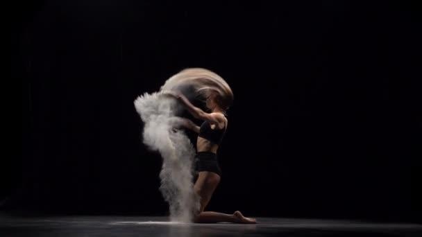 Pomalý pohyb profesionální tanečnice házení prachových částic do vzduchu.