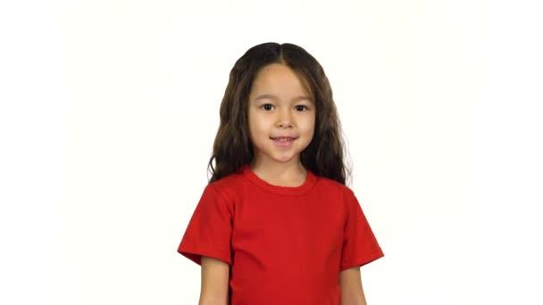 Porträt eines kleinen dunkelhaarigen Kindes, das mit der Hand auf weißem Hintergrund wedelt