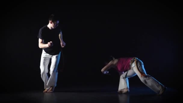 Man and woman performing complex of martial art of capoeira. Slow motion.