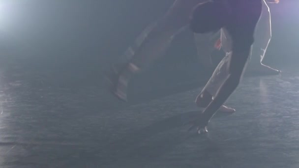 Strong guys practicing capoeira in darkness against spotlight in studio. Close-up slow motion