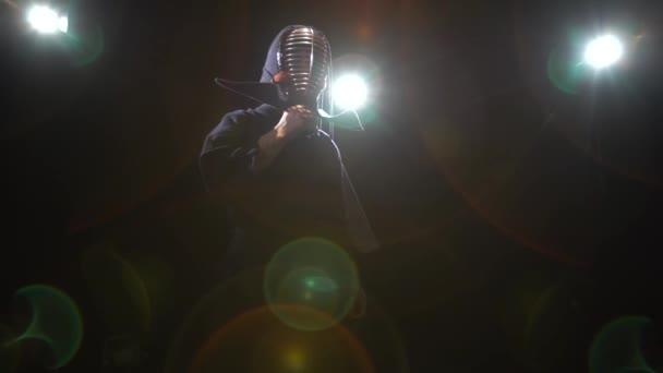 Athletic Kendo oktató pózol a kamera szürkületben.