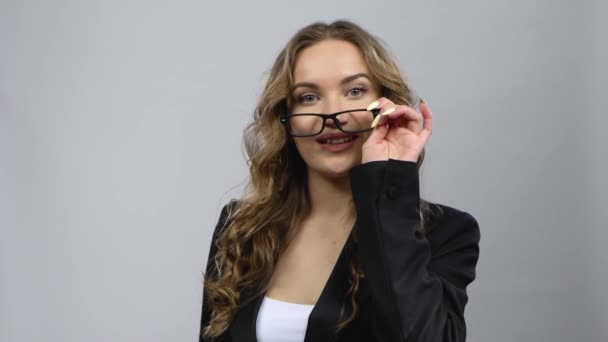Portrét dívky se kudrnatými vlasy v obchodní, opravování brýlí a mrknutí