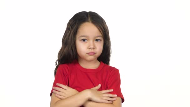 Little girl crosses hands posing at white background. Slow motion