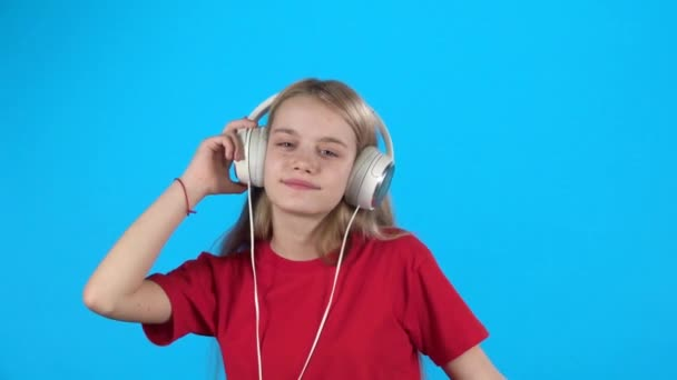 Teen listening to music in big white headphones, singing and dancing. Slow motion