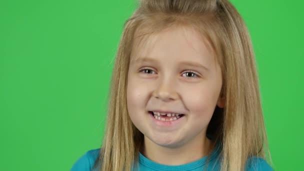 Blízkou dívku, která se směje a dívá se na kameru. Zpomaleně