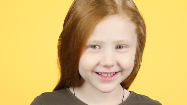 Close-up red-haired child smiling at camera on yellow background. Slow motion