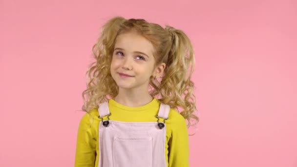 kleine weibliche Cutie im Studio auf rosa Hintergrund mit nachdenklichem und lächelndem Gesicht